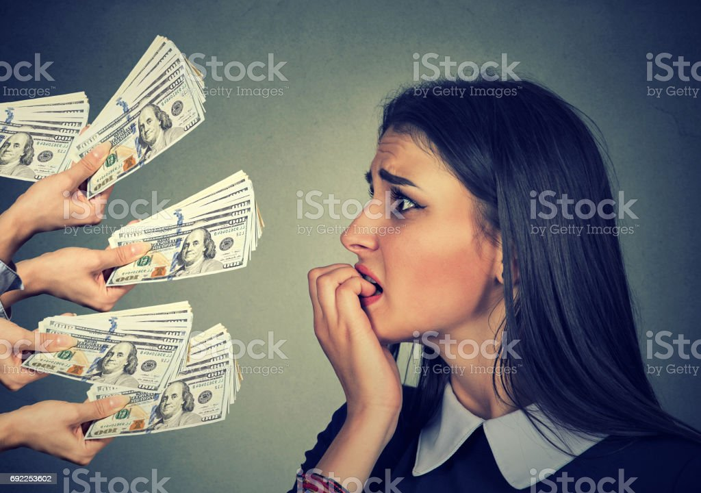 Anxious woman looking at money dollar banknotes offered by suspicious people stock photo