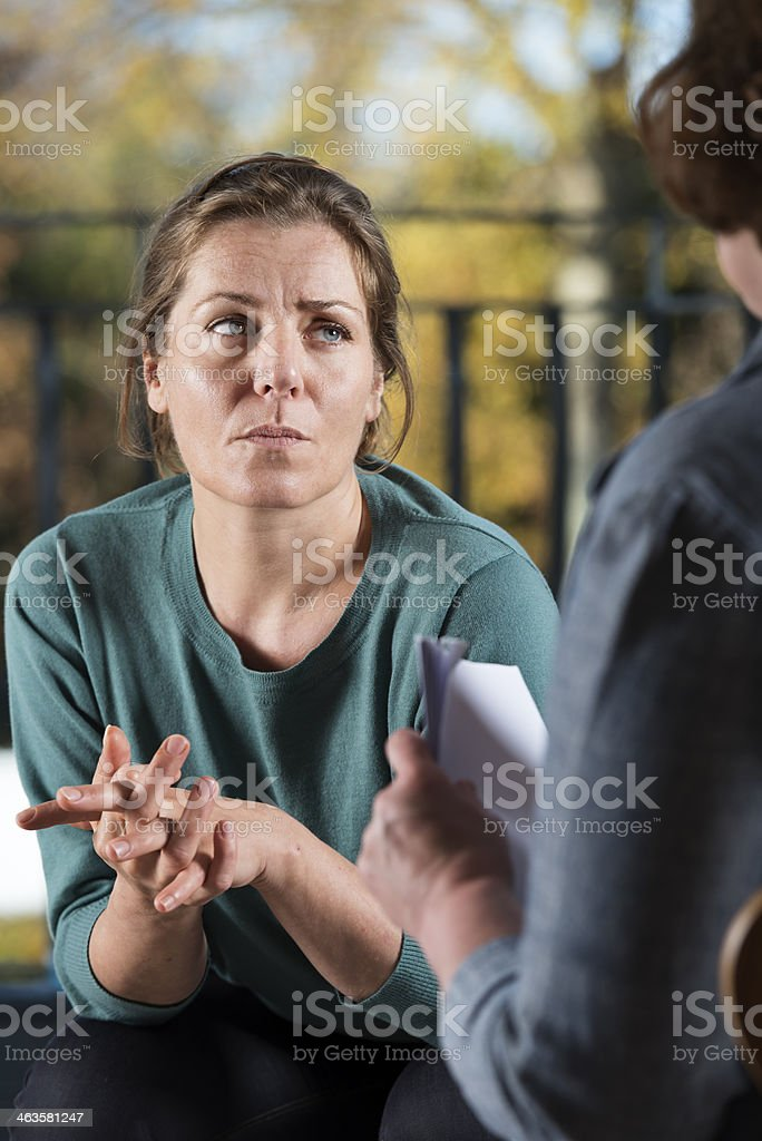 Anxious Woman Talking To a Colleague. stock photo