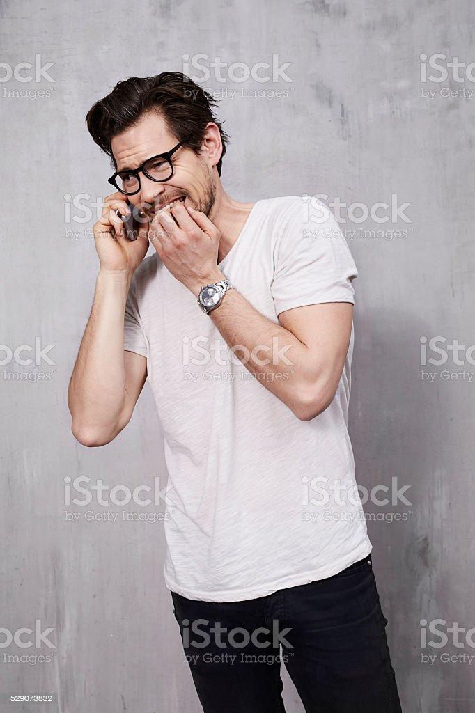 Anxious young man biting fingernails on phone call stock photo