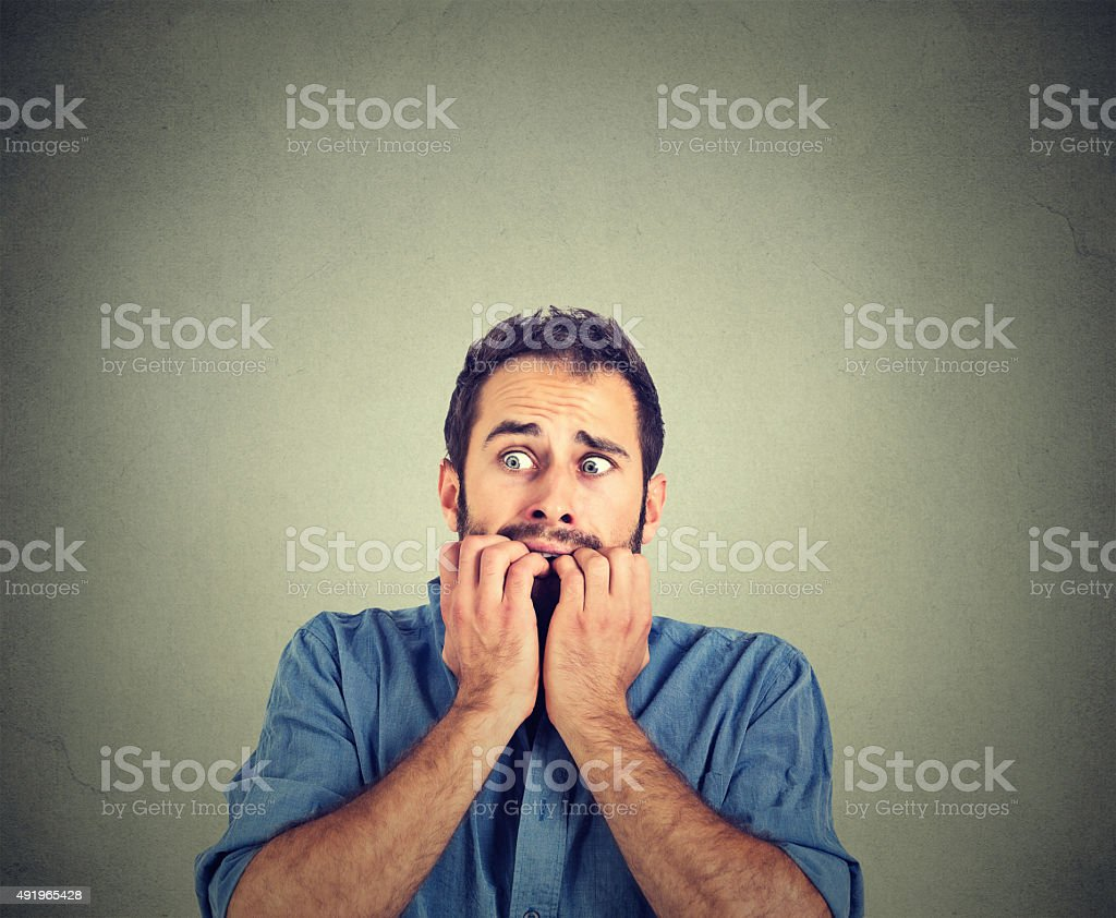 Anxious young man biting his nails fingers freaking out stock photo