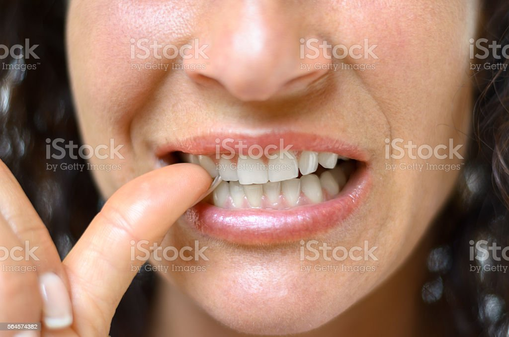 Anxious young woman biting her thumb stock photo
