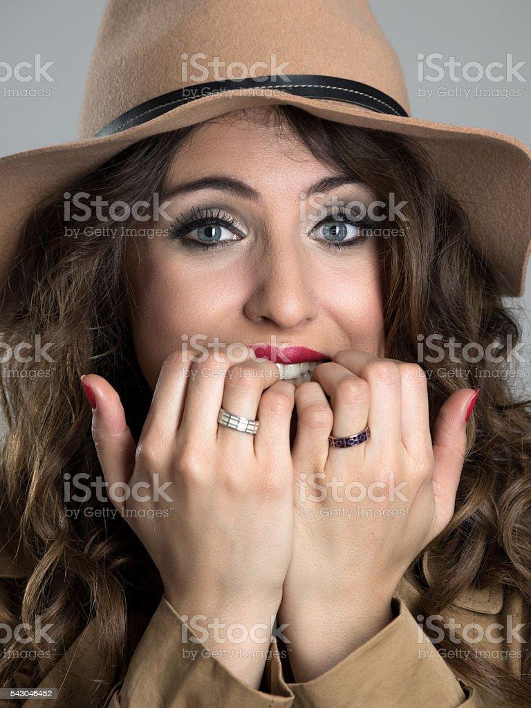 Anxious young woman wearing hat biting fingernails stock photo