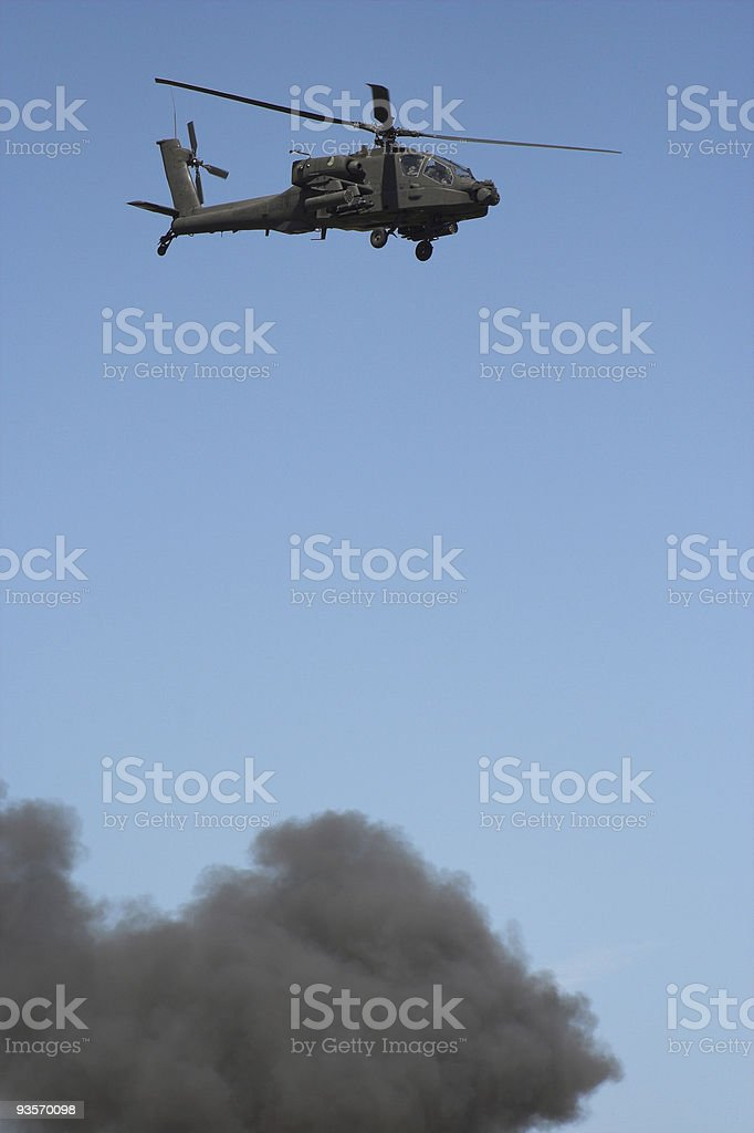 Apache helicopter in flight in a warzone stock photo