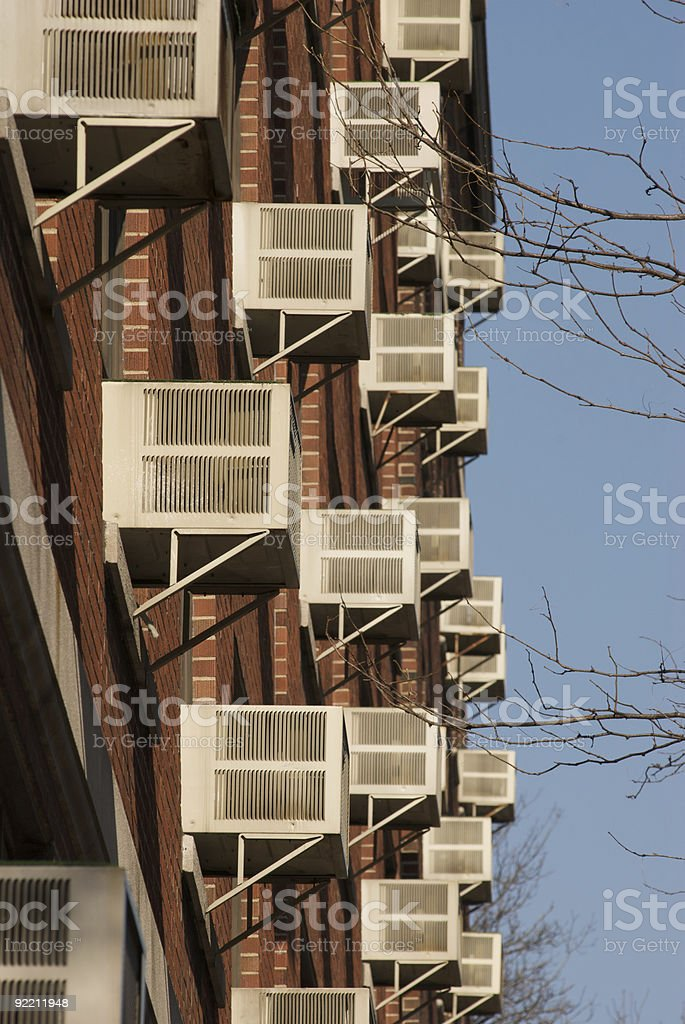 A apartment building with many air-conditioning units stock photo