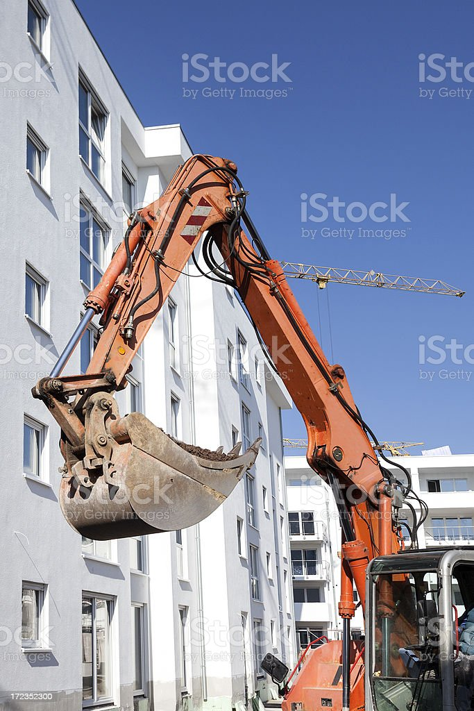 Apartment houses under construction, excavator royalty-free stock photo