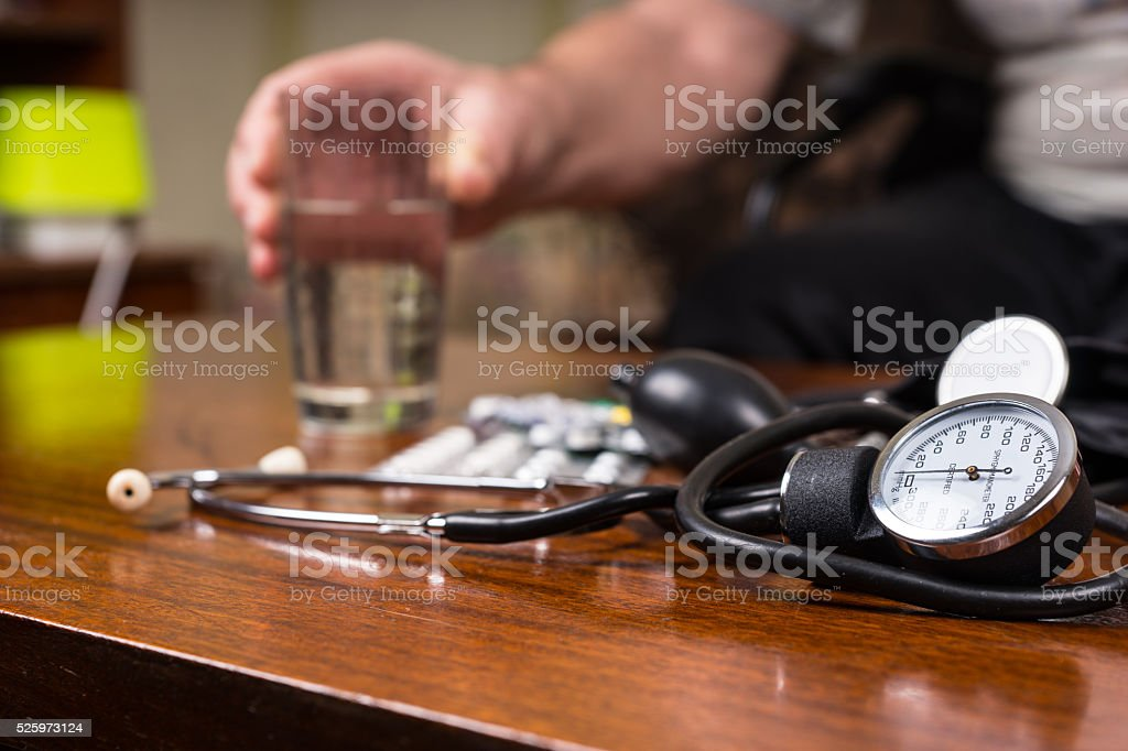 BP Apparatus on the Table with Medicines and Water stock photo
