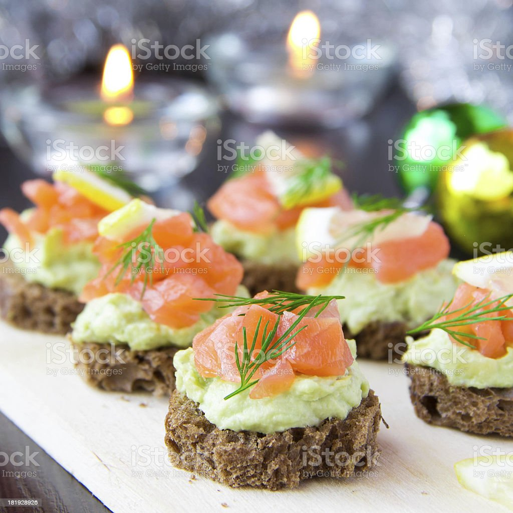Appetizer canapes of bread with avocado, red fish salmon, lemon stock photo