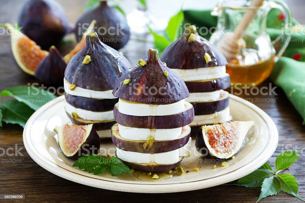 Appetizer of figs and brie cheese with honey. stock photo