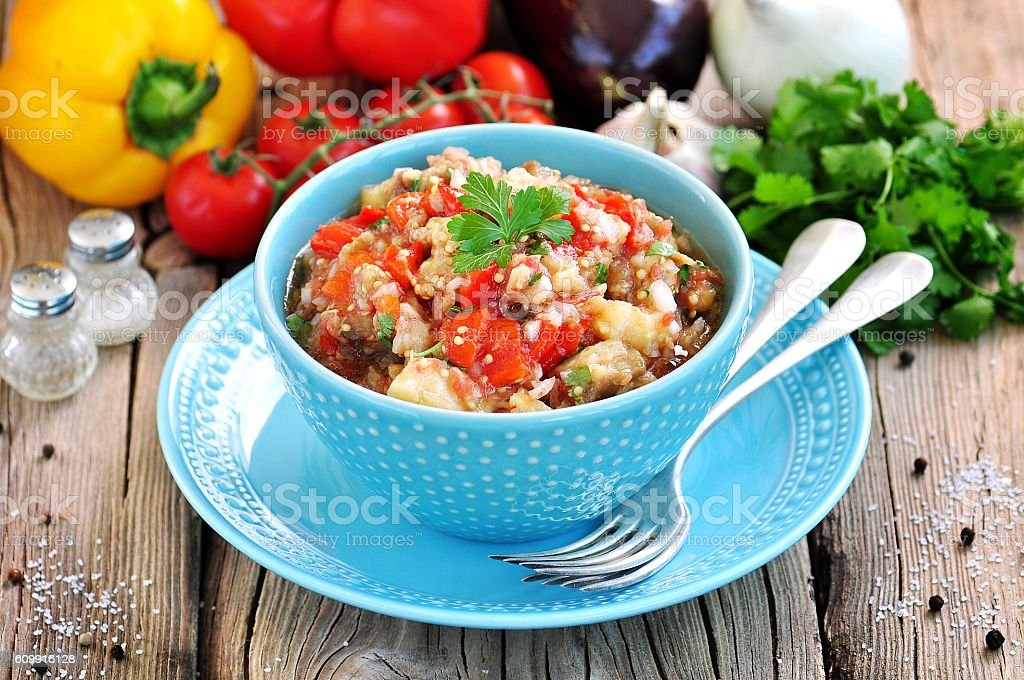 Appetizer (salad) of roasted eggplant, peppers, tomatoes, onions, garlic, coriander. stock photo