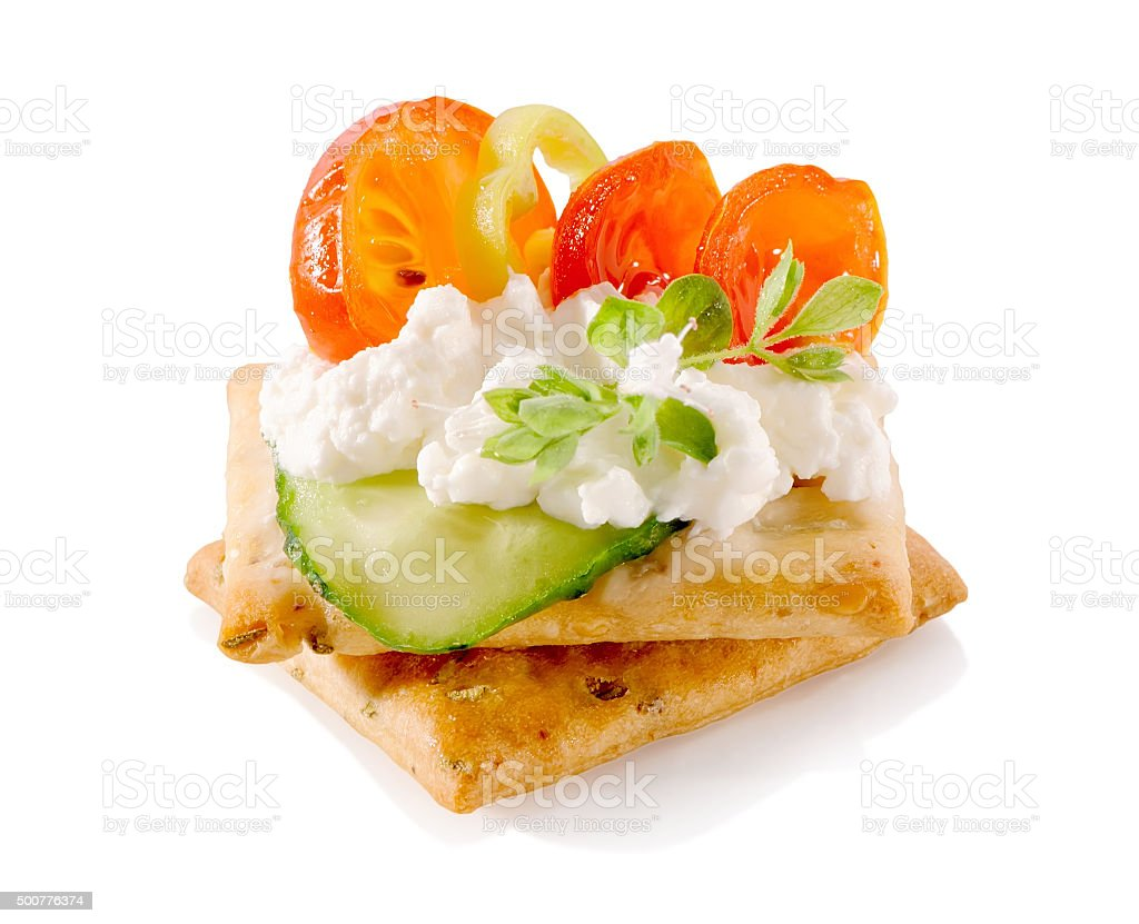 appetizer on crackers with cream cheese and vegetables close-up isolated stock photo