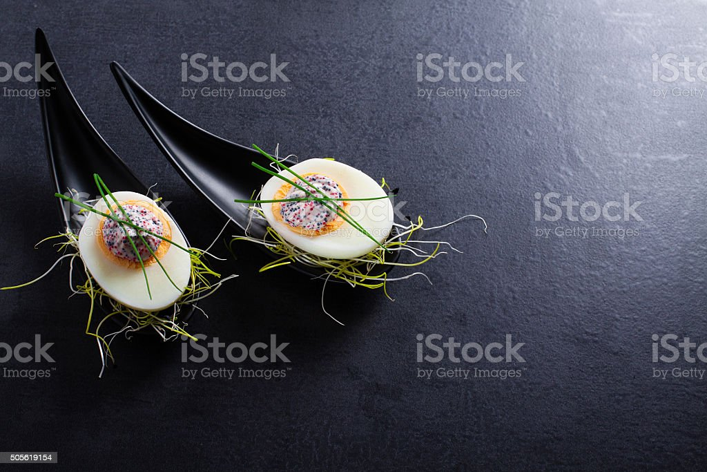 Appetizer on fingerspoon egg with caviaron black background. stock photo
