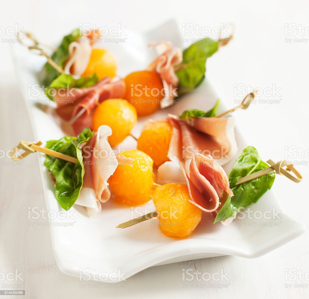 Appetizer with melon and prosciutto on skewers stock photo