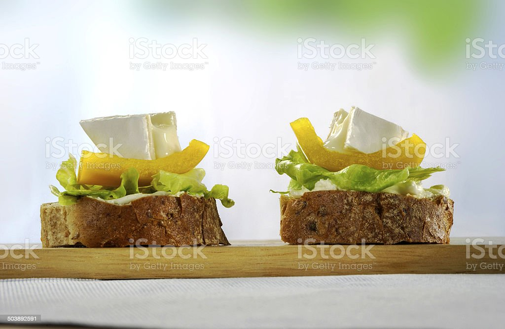 Appetizers of wholemeal bread with cheese and pepper salad stock photo