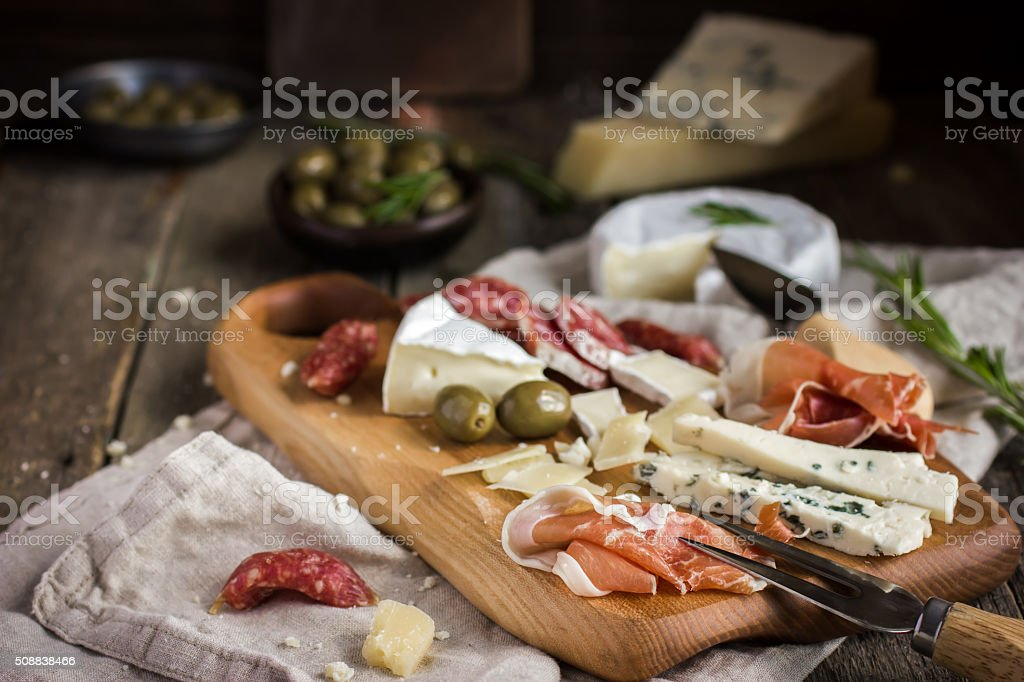 Appetizers. Various types of cheese, salami and prosciutto on  w stock photo