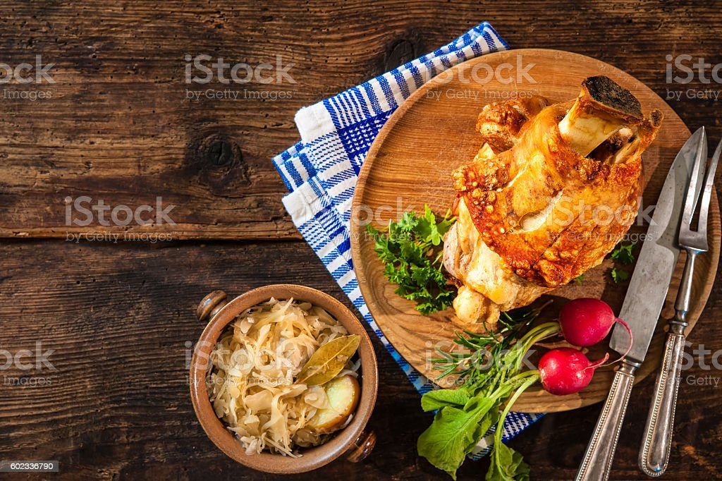 Appetizing Bavarian grilled pork knuckle with sauerkraut stock photo