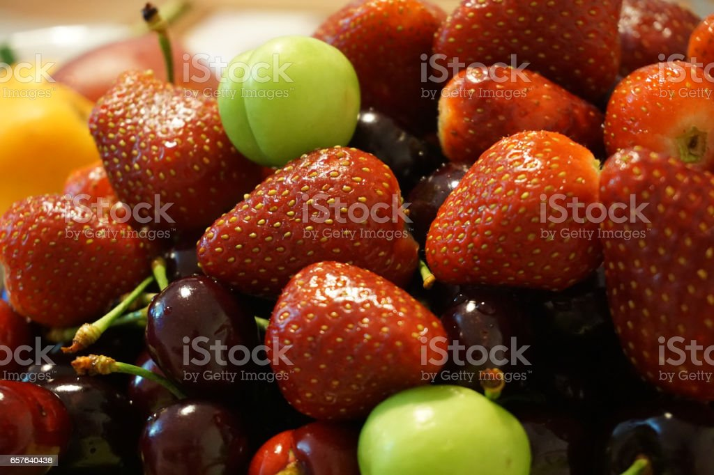 Appetizing fresh fruit plate with strawberry cherry plum stock photo