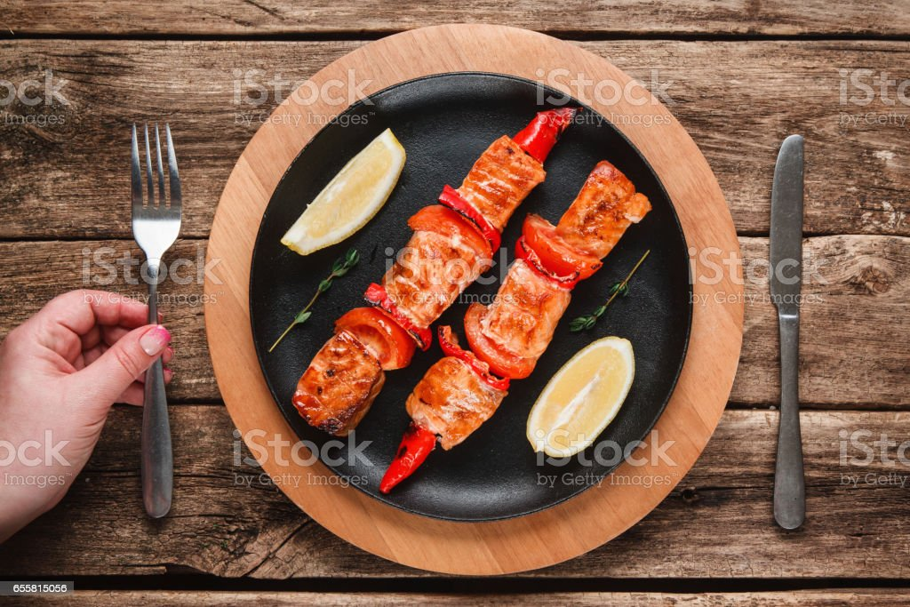 Appetizing grilled fish. Delicious salmon kebab. stock photo