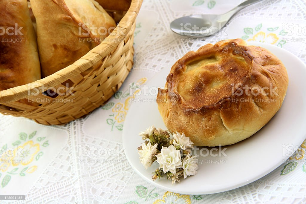 Appetizing pie and basket of patty in the tablecloth stock photo