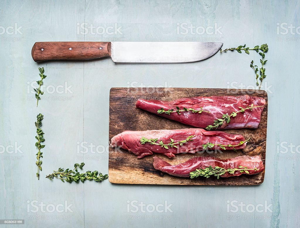 appetizing pieces raw lamb herbs  knife  cutting board  close up stock photo