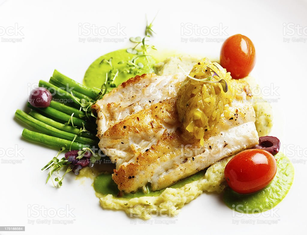 Appetizing restaurant entree of grilled fish, lentl puree and vegetables stock photo