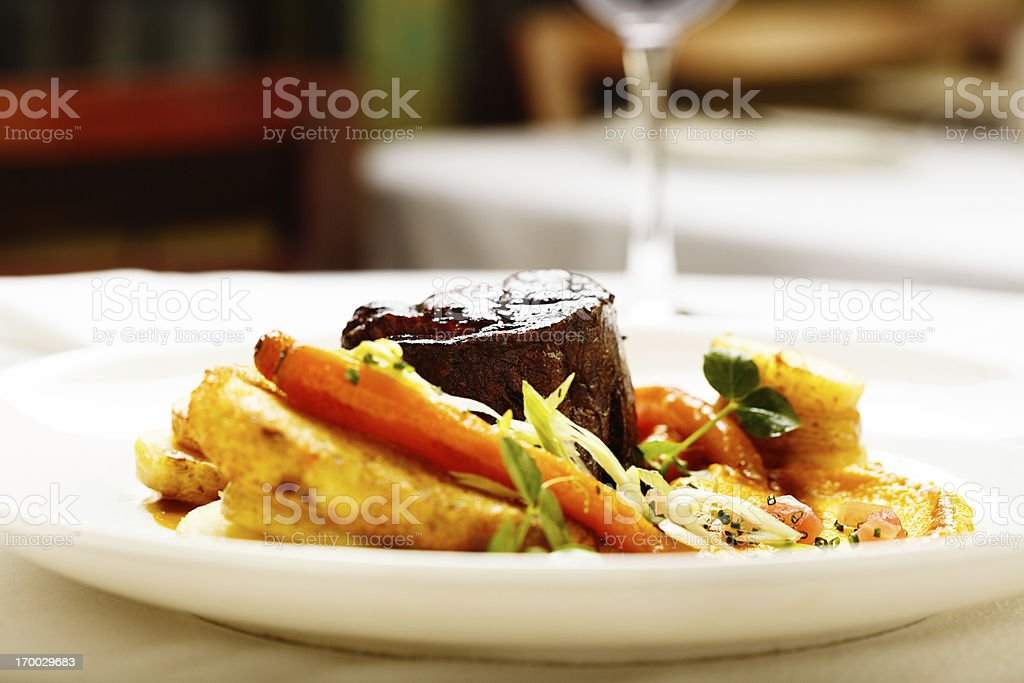 Appetizing restaurant entree of seared steak and glazed vegetables stock photo