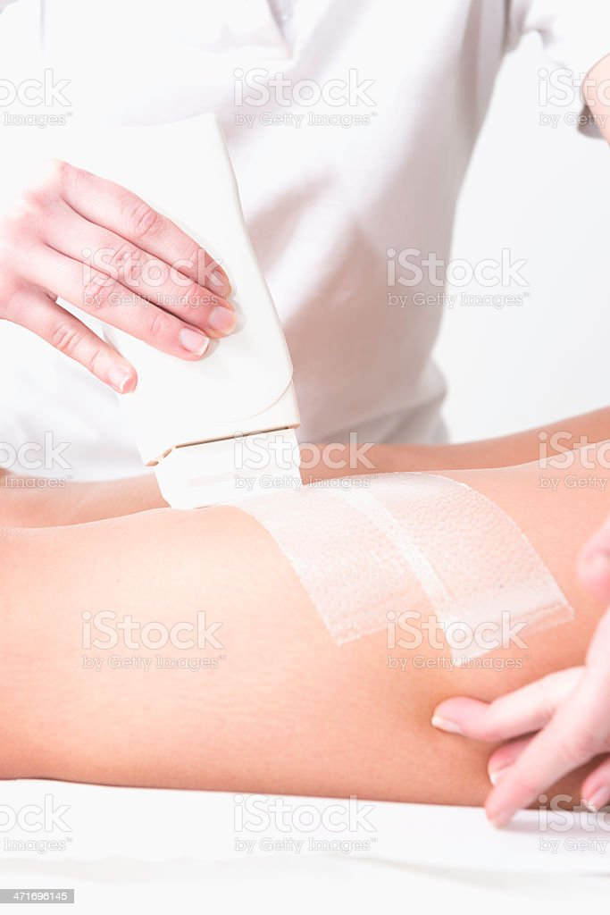 Applaying depilation wax on woman's leg royalty-free stock photo