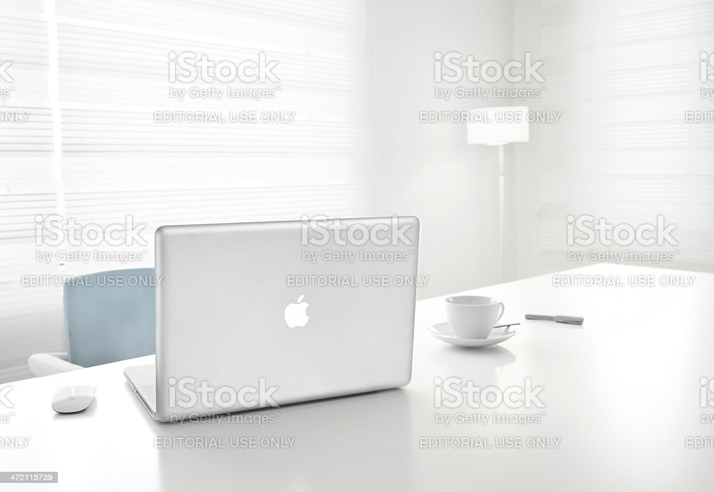 Apple 17-inch MacBook Pro and magic mouse in office stock photo