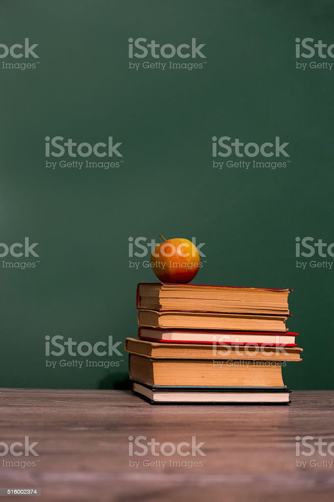Apple and book on wooden table stock photo