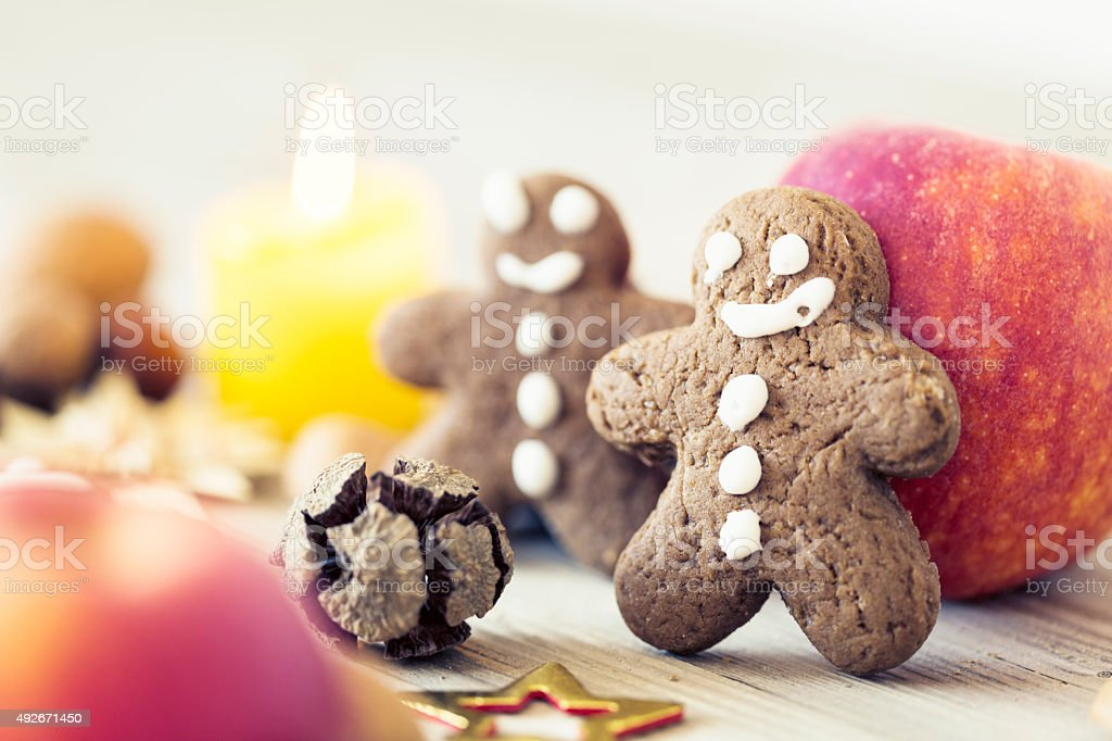 apple and gingerbread men candle light stock photo