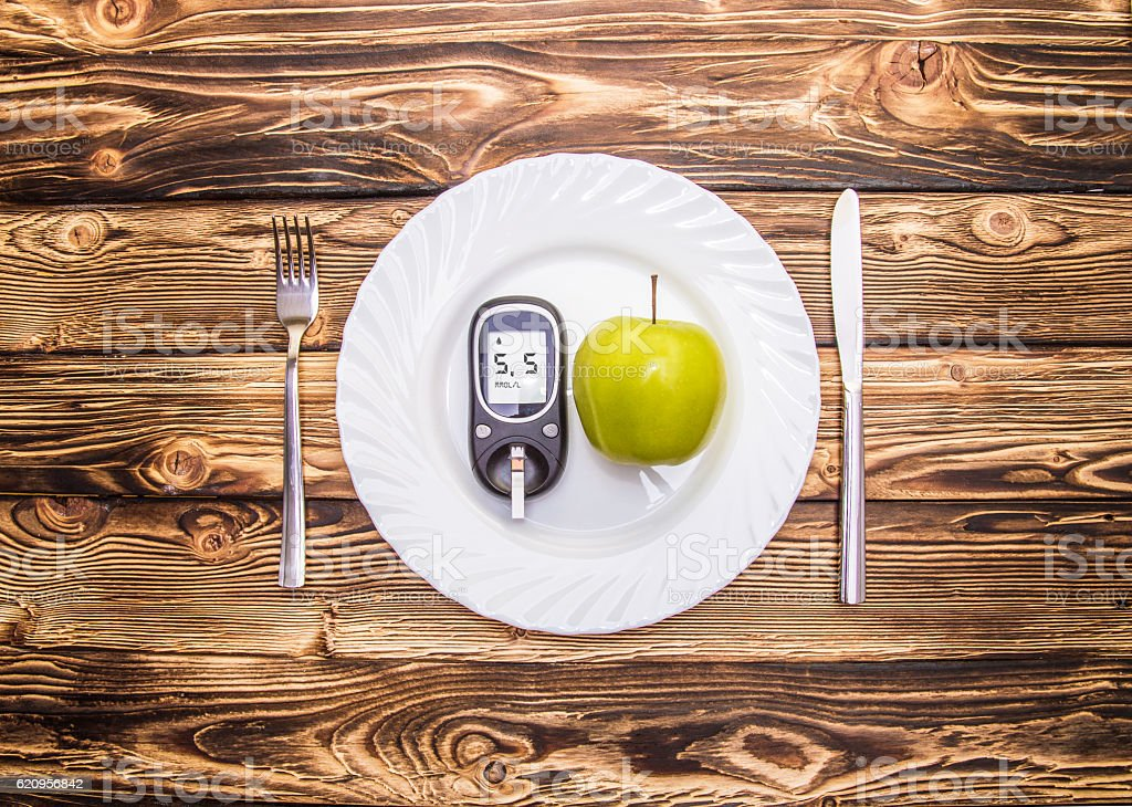 Apple and glucometer to measure blood sugar on a plate stock photo