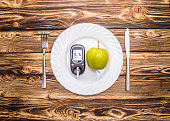 Apple and glucometer to measure blood sugar on a plate