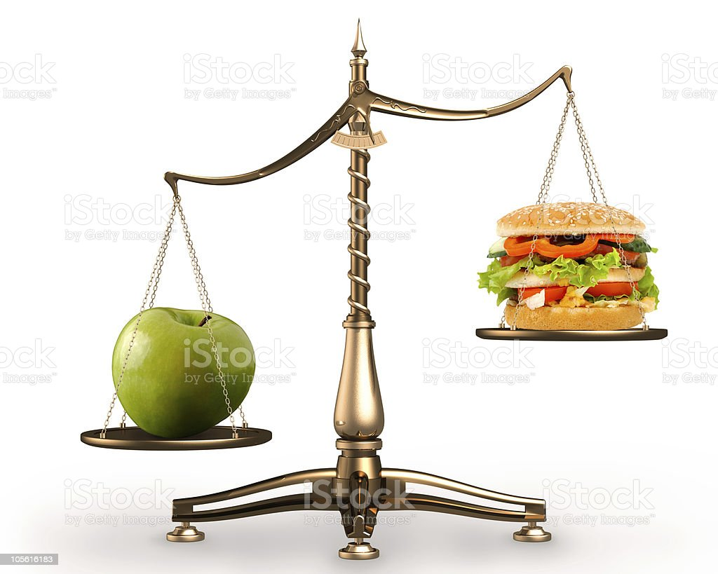 Apple and hamburger on scales conceptual stock photo