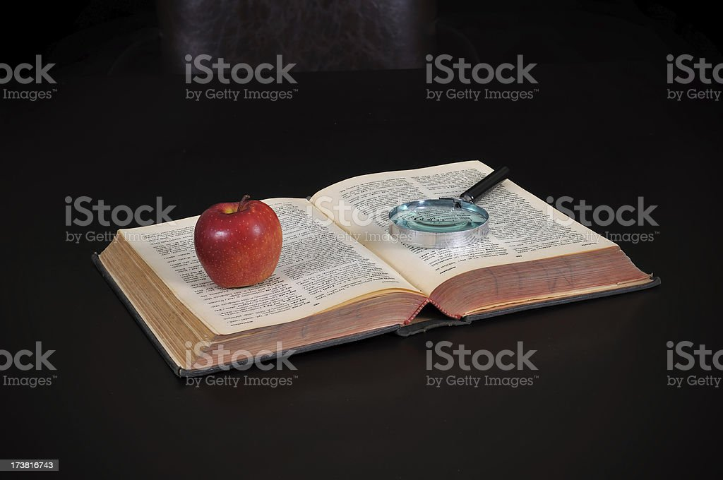 apple and magnifying glass on the book royalty-free stock photo