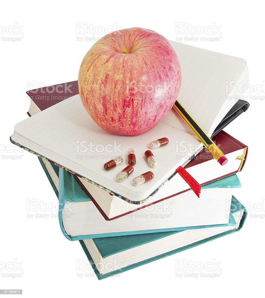 Apple and pills on big pile of books royalty-free stock photo