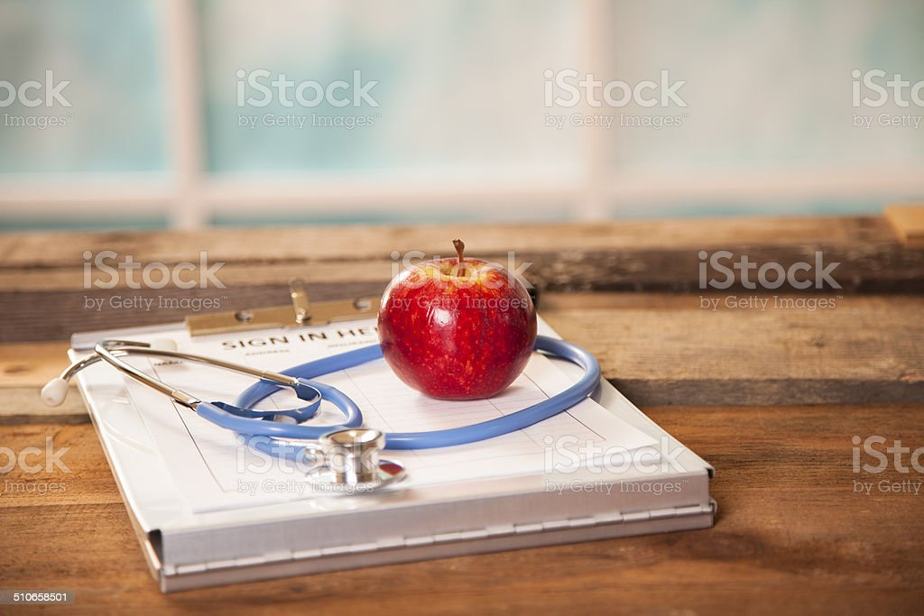 Apple and stethoscope on top of doctor's office registration form. stock photo