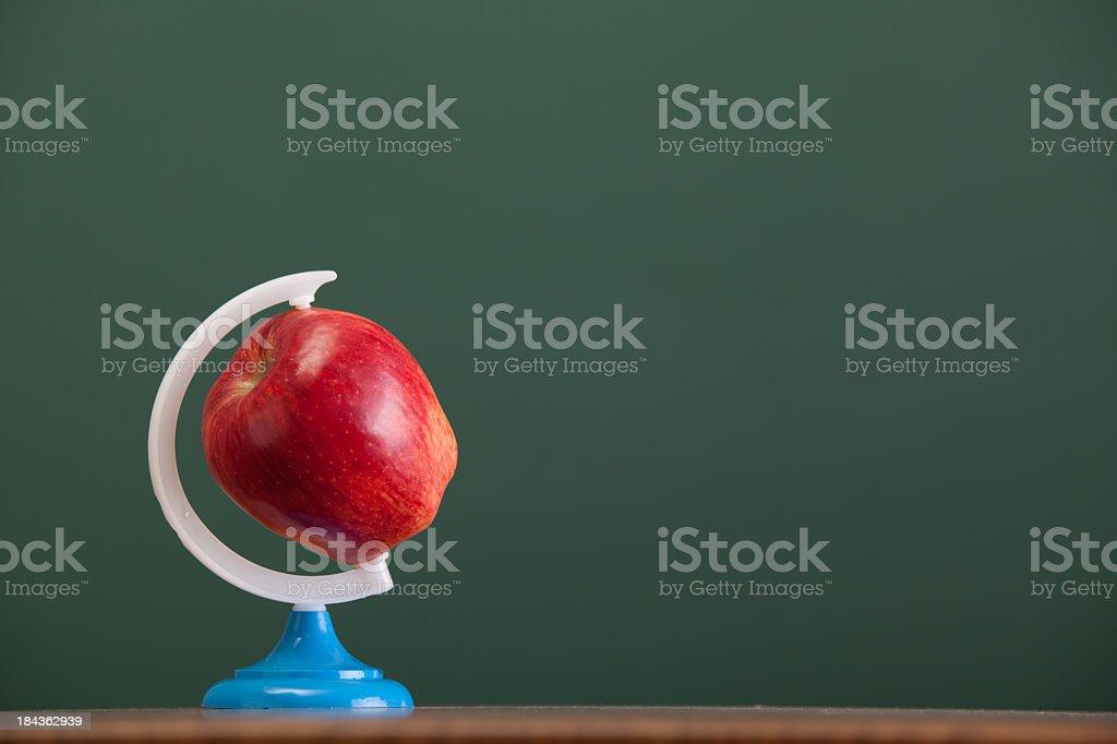 Apple as globe before green chalkboard stock photo