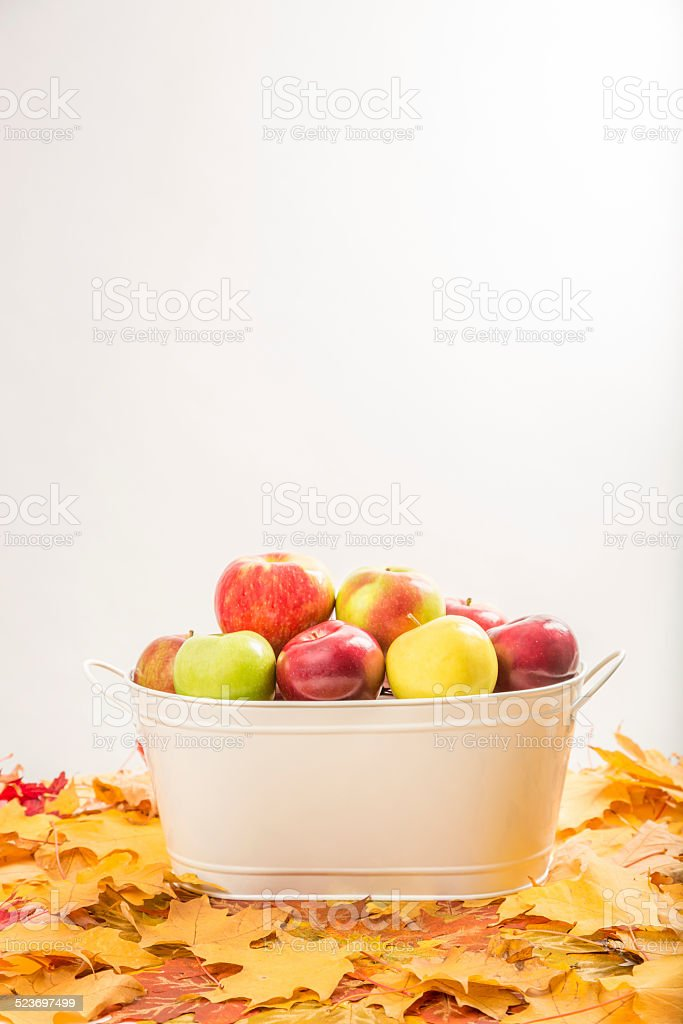 Apple basket on bed maple leafs stock photo