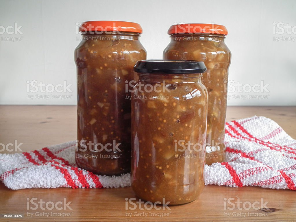 Apple chutney in jars, on a pine table stock photo