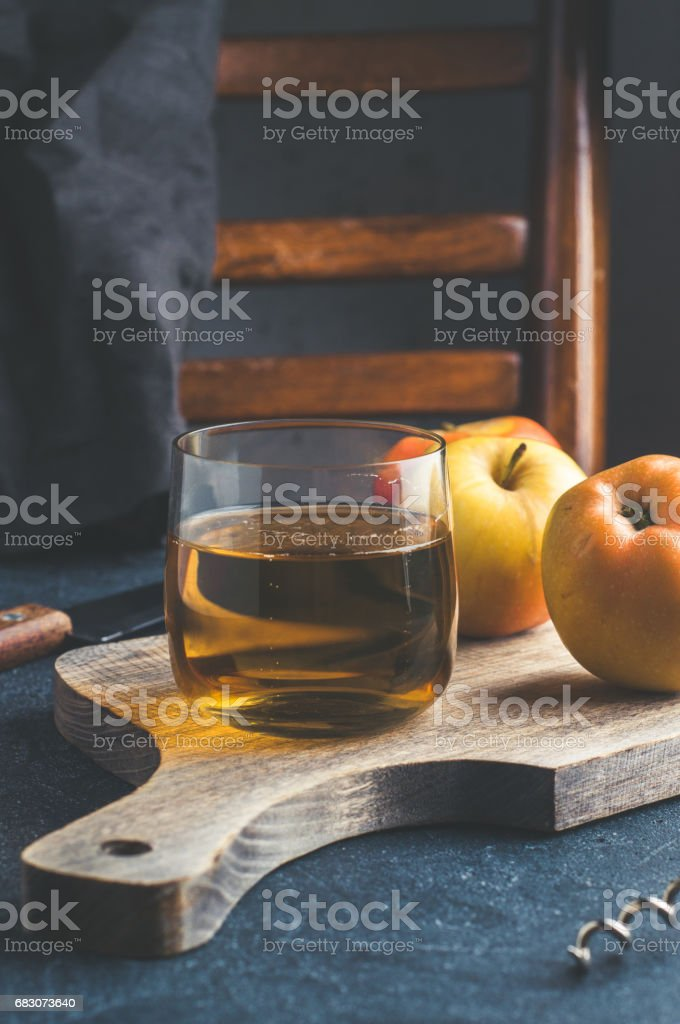 Apple cider in a glass and fresh apples on dark stone background. Vertical cropping stock photo