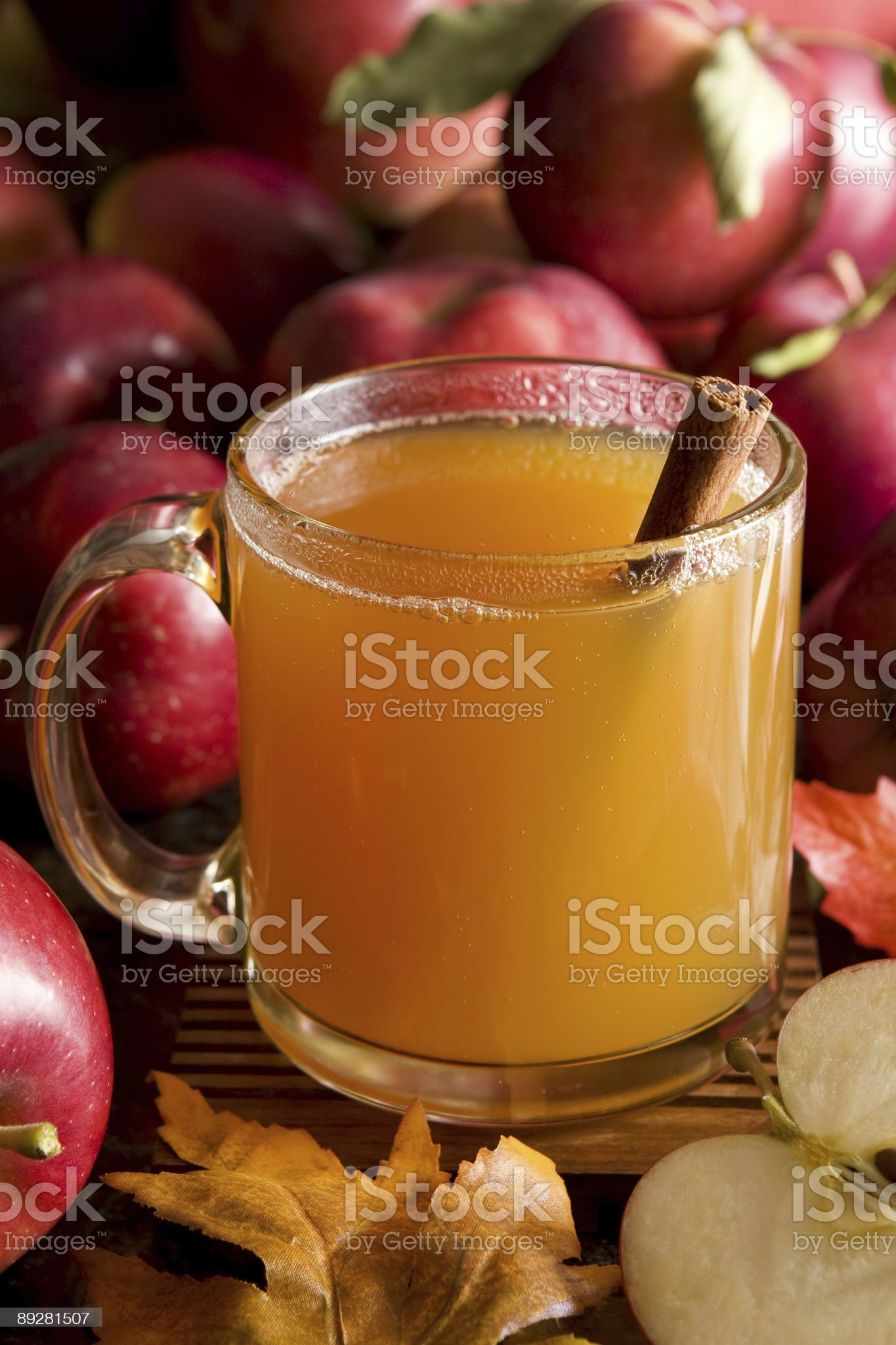 Apple cider in glass mug with cinnamon stick next to apples royalty-free stock photo