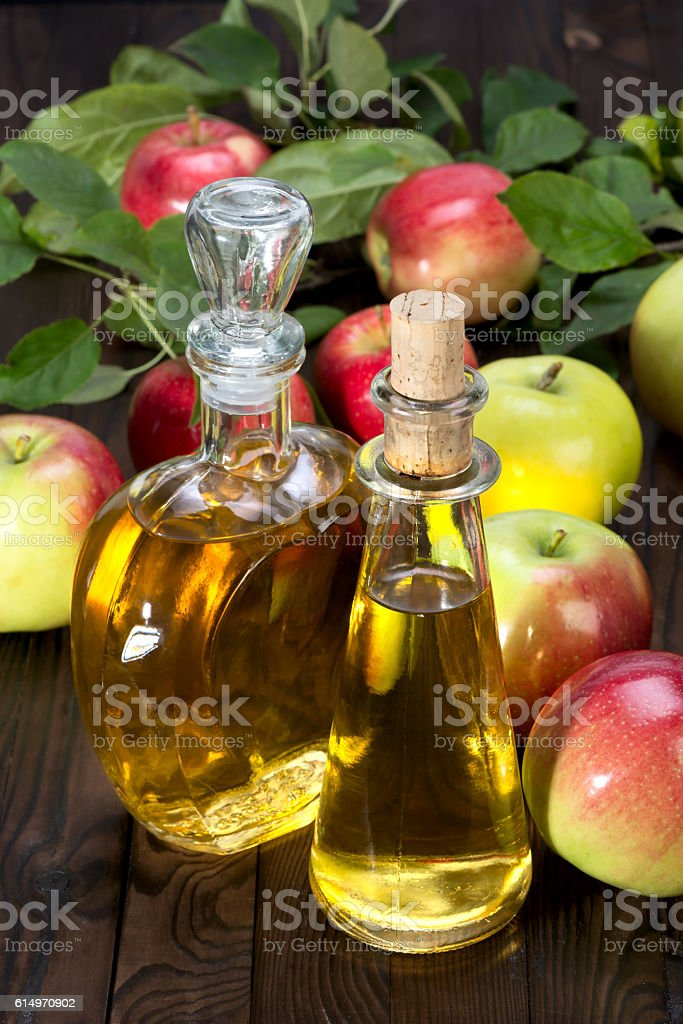 apple cider vinegar in a glass vessel and apples stock photo