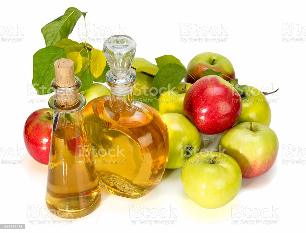 apple cider vinegar in glass vessel. red and green apples stock photo