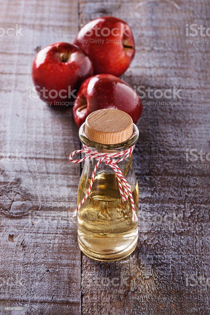 Apple cider vinegar over rustic wooden background stock photo