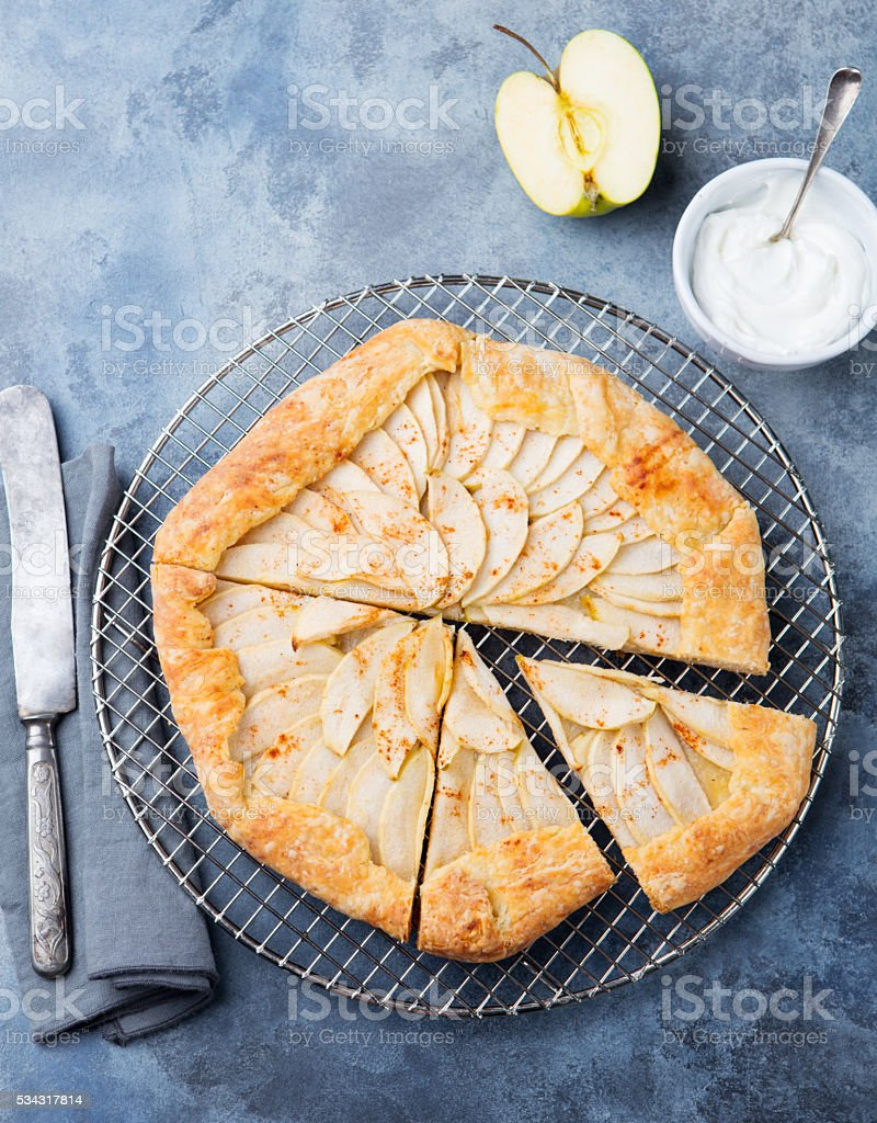Apple galette, pie, tart with cinnamon on cooling rack stock photo
