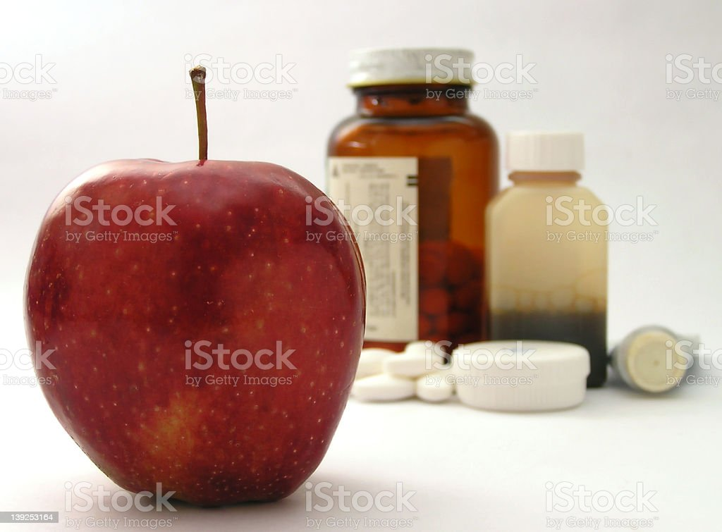 Apple in foreground with pills and medicine in background stock photo