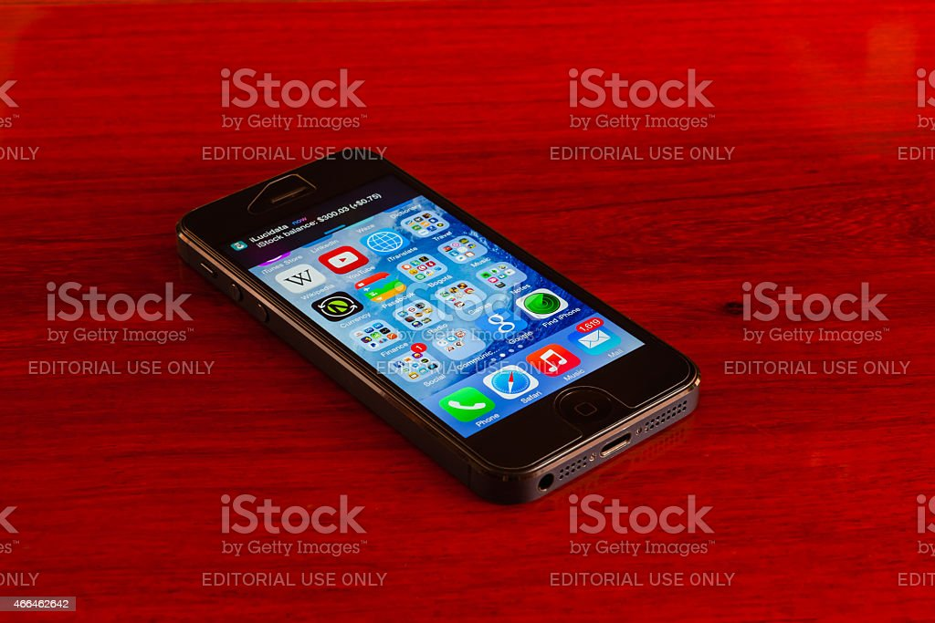 Apple iPhone 5 - on rich rosewood furniture stock photo
