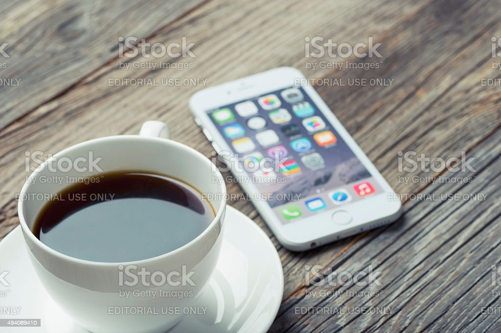 Apple iphone 6 on a wooden table with coffee. stock photo