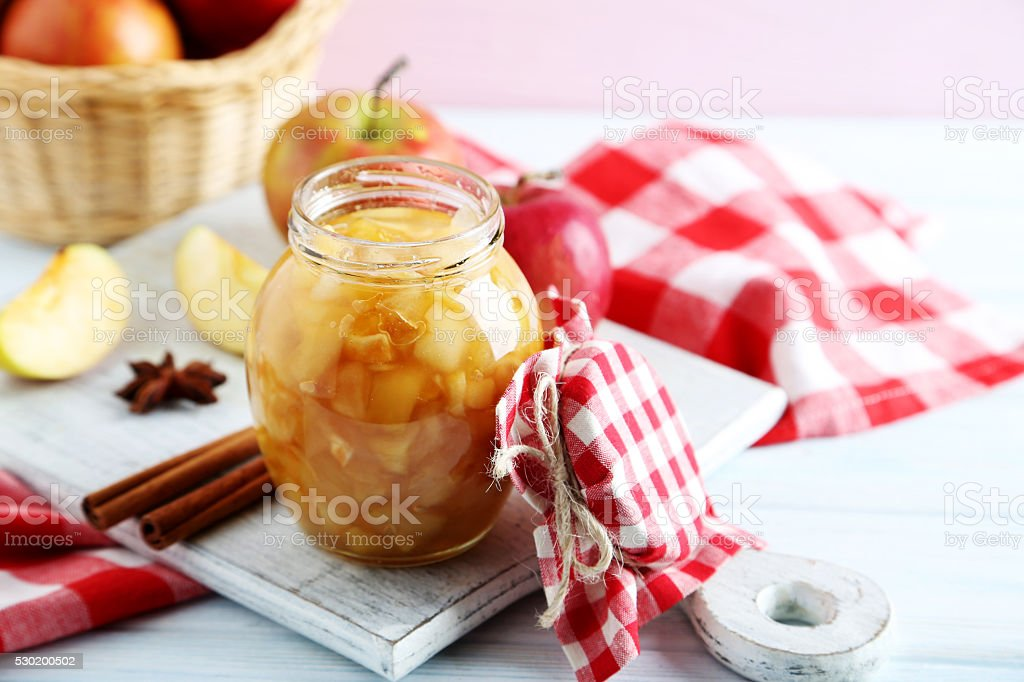 Apple jam in jar on a white wooden table stock photo