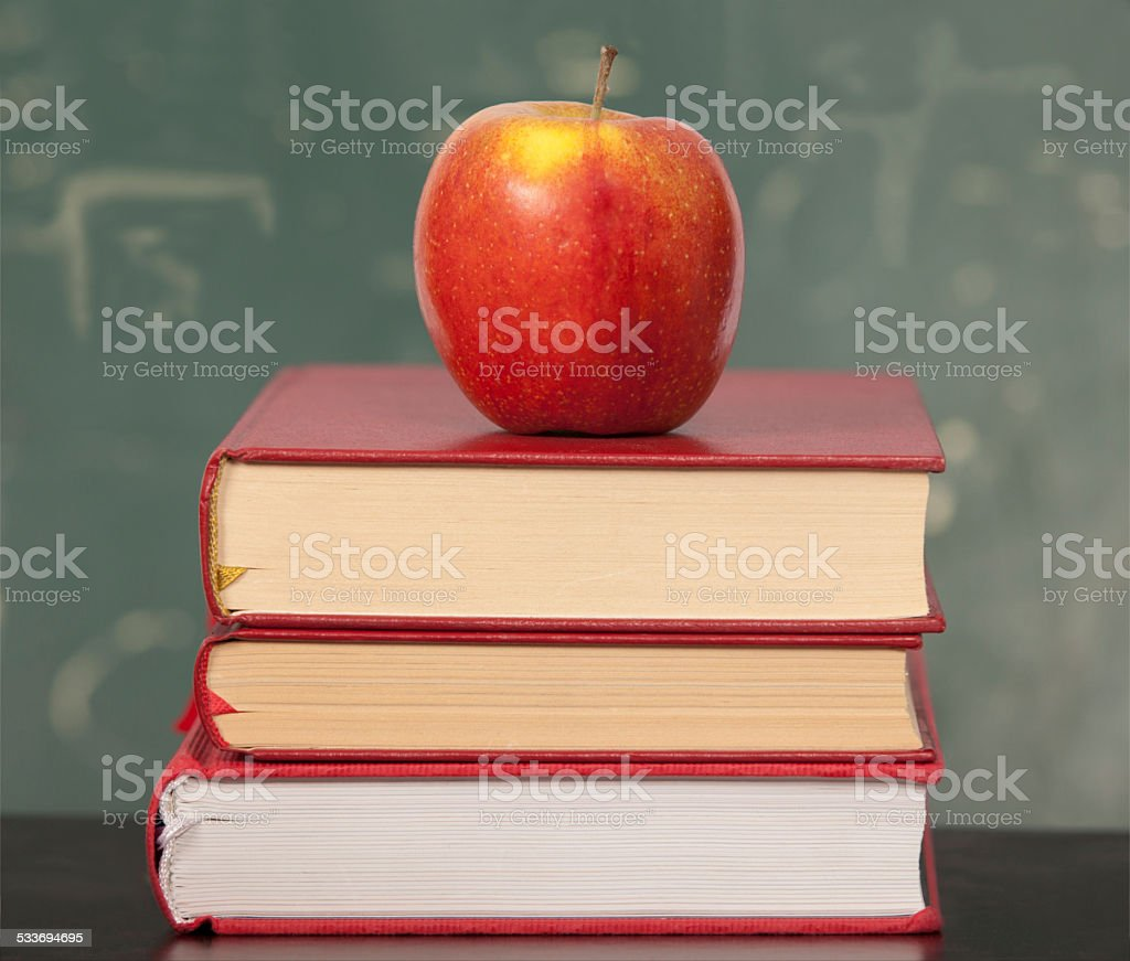Apple laying on a staple of Books stock photo