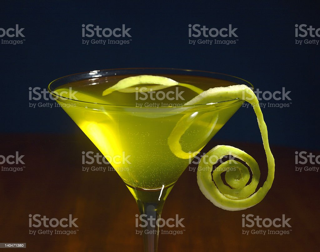 Apple martini with curled garnish on side stock photo